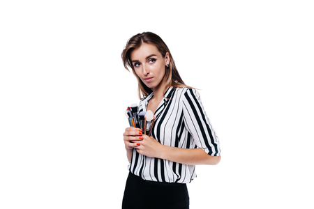 beautiful girl with big eyes, professional make-up artist in a striped shirt on a white background
