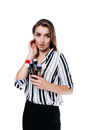 beautiful girl with big eyes, professional makeup artist in a striped shirt on a white background holding brushes