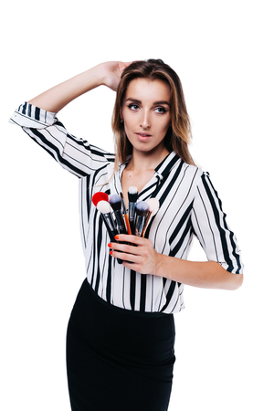 beautiful girl with big eyes, professional makeup artist in a striped shirt on a white background holding multicolored tassels Фото со стока