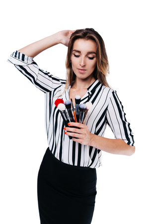 beautiful girl with big eyes, professional makeup artist in a striped shirt on a white background looks at the tassels Фото со стока