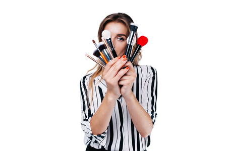 beautiful girl with big eyes, professional make-up artist in a striped shirt on a white background looks through the tassels with his eye into the camera Фото со стока