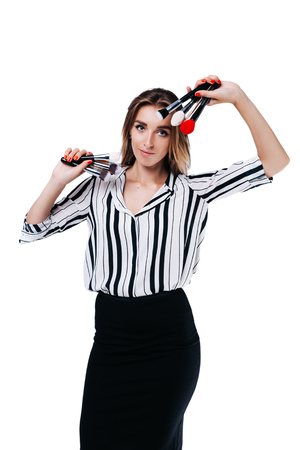 makeup artist girl in a black skirt and a striped shirt shows makeup brushes on a white background Фото со стока