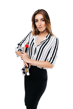 portrait of a girl on a white background in a striped shirt and black skirt holding makeup brushes