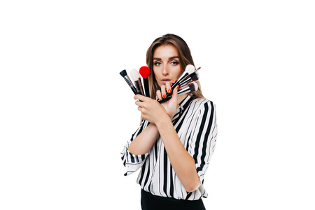 makeup artist girl on a white background holding different brushes