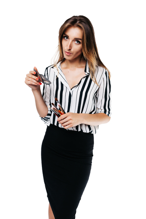 makeup artist girl in shirt and black skirt on a white background holding small eye shadow brushes and a palette in her hands