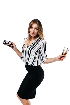 cheerful girl makeup artist in shirt and black skirt on a white background holding small eye shadow brushes and a palette Фото со стока