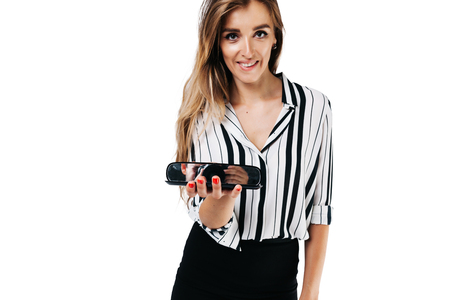 smiling girl makeup artist in shirt and black skirt on a white background holding a small mirror in which a photographer
