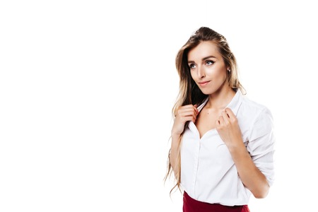 girl in white shirt and burgundy skirt on an isolated white background holding on to her shirt Фото со стока