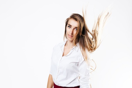 girl in a white shirt and burgundy skirt on an isolated white background, with a flying hairstyle Фото со стока