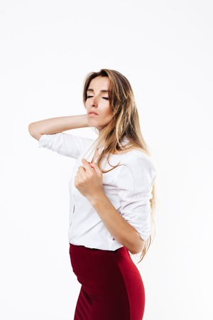 girl in a white shirt and burgundy skirt on an isolated white background, with closed eyes Фото со стока