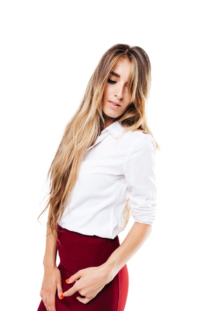 girl in a white shirt and burgundy skirt on an isolated white background, looking down