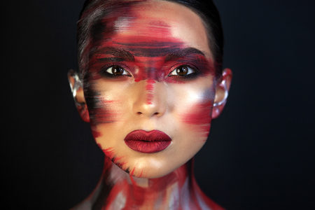 Porter Eurasian girls with dark hair and clear skin, and brown eyes, on a black background, in makeup red ottenkami on the face in the form of strokes, and delicate red lips Фото со стока