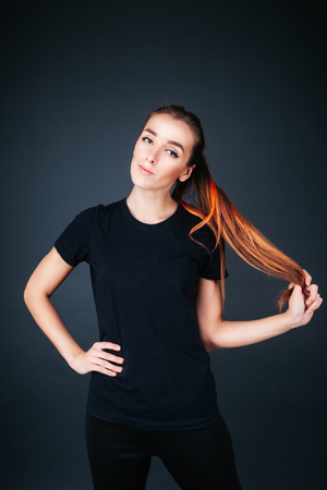 sporty-looking girl in a black T-shirt and leggings on a dark background holding herself by the hair Фото со стока