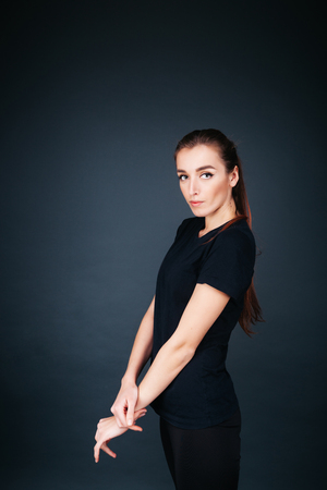 sporty-looking girl in a black T-shirt and leggings on a dark background looking into the camera