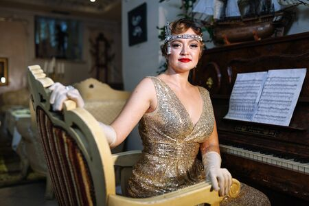 30-year-old woman in a glamorous style with red lipstick in a gold dress with a diadem on her head sits behind a pionino, looks at the camera and smiles slightly