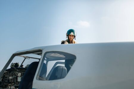 close-up of a girl in a helmet piercingly looks into the camera, by the plane