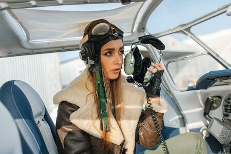 Close-up of a female aviator in a headdress with glasses speaks into the microphone from the headphones inside the plane