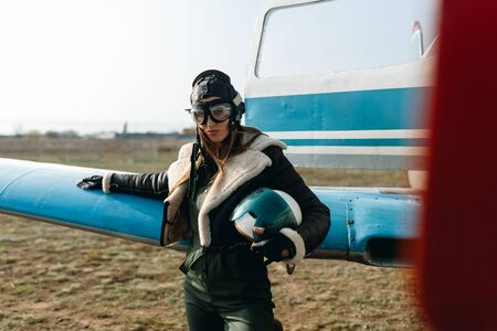 a girl with glasses and a headdress holds a helmet in her hands, in the background of the plane she is dressed in a warm leather jacket, gloves, green overalls