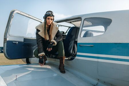 girl in a headdress with glasses, squatting on the wing of an airplane