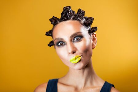 close-up of a girl on a yellow background of Caucasian-Asian appearance with a creative hairstyle in the form of horns and yellow lips, makes the emotion of a smirk