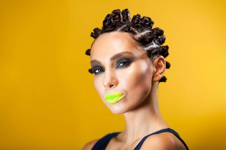 portrait of a girl on a yellow background of Caucasian-Asian appearance with a creative hairstyle in the form of horns and yellow lips, stares intently at the camera