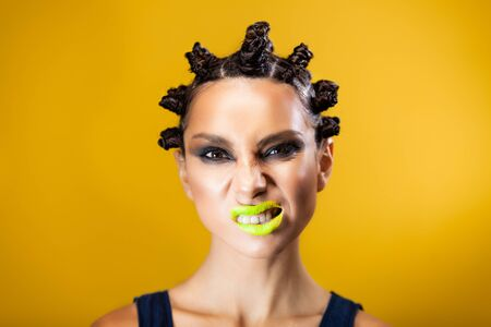 portrait of a girl on a yellow background of Caucasian-Asian appearance with a creative hairstyle in the form of horns and yellow lips, getting angry showing teeth and grimace