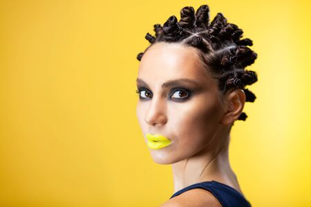 portrait of a girl on a yellow background with an original creative afro hairstyle in the form of horns, looking at the camera half a turn