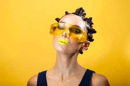 portrait of a girl on a yellow background with the original creative afro hairstyle in the form of horns, in yellow construction glasses looks at the camera Archivio Fotografico