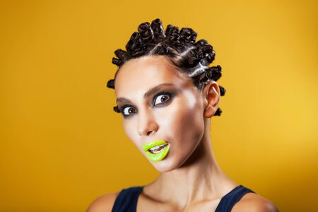 portrait of a girl on a yellow background of Caucasian-Asian appearance with a creative hairstyle in the form of horns and yellow lips, making an emotion open mouth surprise
