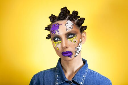 portrait of a girl on a yellow background with an original creative afro hairstyle in the form of horns, with colored blots on her face looks with her unreal eyes into the camera