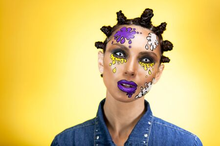 portrait of a girl on a yellow background with an original creative afro hairstyle in the form of horns, with colored blots on her face with lenses on her eyes opened her mouth