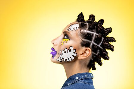 profile of a girl on a yellow background with an original creative afro hairstyle in the form of horns, with colored blots on the face with lenses and violet lips