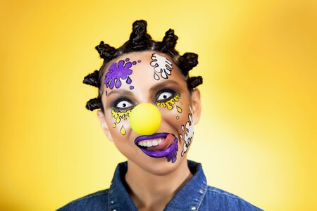 portrait of a girl with colored blots on her face on a yellow background with an original creative hairstyle in the form of horns in the Afro style, smiling and licking her teeth