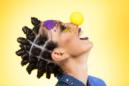 in profile a girl with colored blots on her face on a yellow background with an original creative hairstyle in the form of horns in the Afro style and a clown nose, have a fun laugh opening her mouth