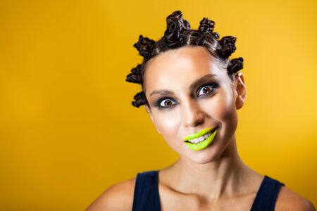 girl on a yellow background with an original creative afro hairstyle in the form of horns, smiling nervously while looking at the camera Archivio Fotografico