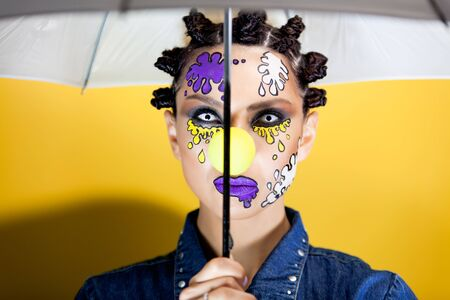 girl on a yellow background with makeup in the form of colored spots, pleasantly looking at the camera holding an umbrella over her head Archivio Fotografico