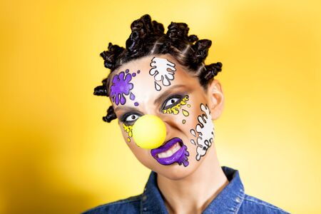 girl on a yellow background with makeup in the form of colored spots, grinning at the camera Archivio Fotografico