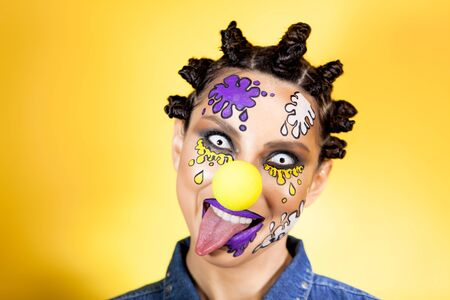 girl on a yellow background with make-up in the form of colored spots, grins tongues out Archivio Fotografico