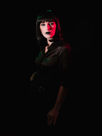 Girl with black makeup and black hair posing on a black background with colored light. Archivio Fotografico