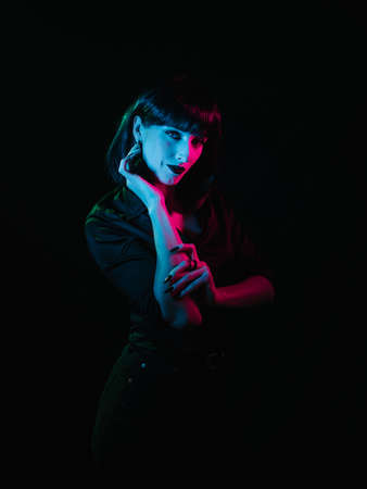 Girl with black hair and black makeup posing on a black background with colored light. She demonstrates her hands and stares at the camera.