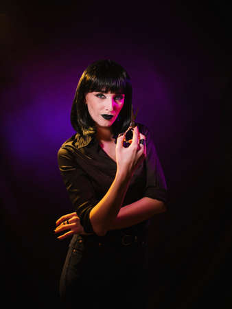 A woman in a black wig and a black, silk shirt, demonstrates open scissors in her hands.