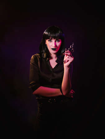 A woman in a black wig and a black, silk shirt demonstrates hairdressing scissors in her hands.