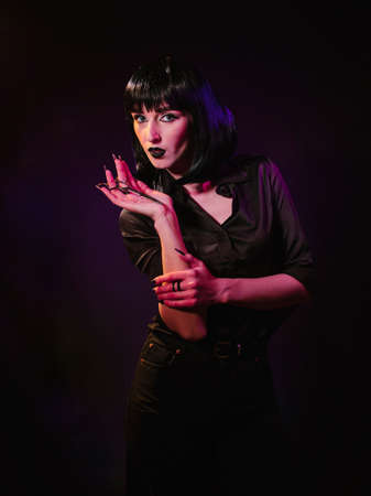 A girl in a black haircut, on a black background with colored light, demonstrates hairdressing scissors on her palm. Archivio Fotografico