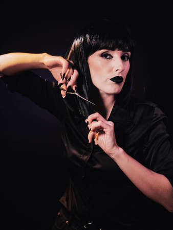 A woman on a dark background with black hair and black lips. holds hairdressing scissors in her hands with which she cuts off a strand of hair from her face.