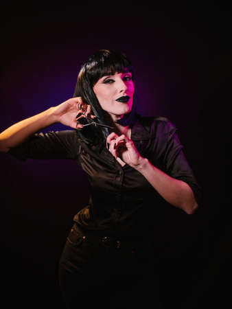 A woman on a dark background with black hair and black lips. holds hairdressing scissors in her hands with which she cuts off a strand of hair from her face
