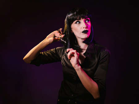 A woman on a dark background with black hair and black lips looks confidently into the camera. She holds a hairdressing scissors in her hands with which she cuts off a strand of hair from her face.