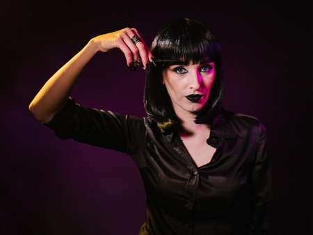 A woman on a dark background with black hair and black lips holds hairdressing scissors in her hands with which she cuts off her bangs.