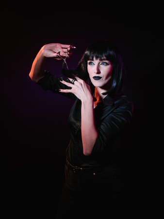 A woman on a black background with a black haircut, black lips, a black silk shirt looks to the side, she holds in her hands hairdressing scissors with which she wants to cut off a lock of her hair.
