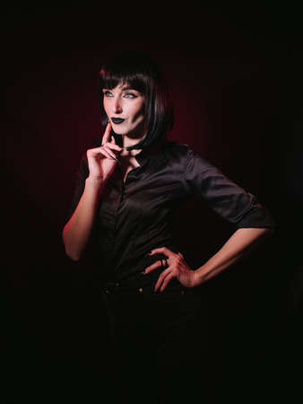 A girl with black hair, dark makeup and black clothes posing with her hands in the frame. Her gaze is directed to the side and expresses thoughtfulness, determination or doubt. Archivio Fotografico