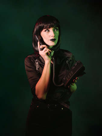 A woman in a black shirt and a harness holds a phone in one hand and a telephone receiver in the other hand, which is brought to her ear, her gaze is directed to the side.